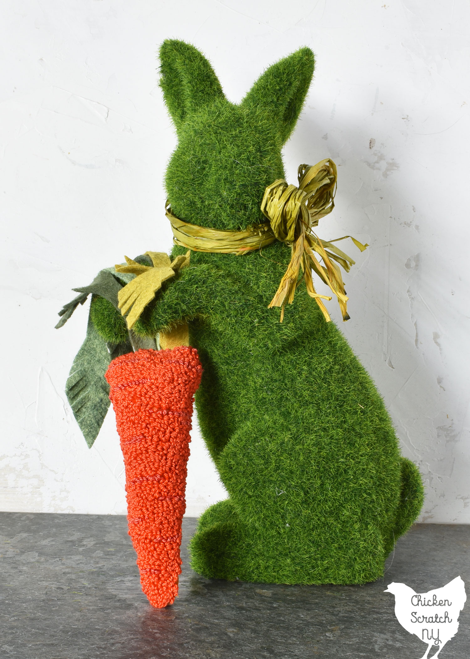 green moss bunny holding an orange punch needle carrot
