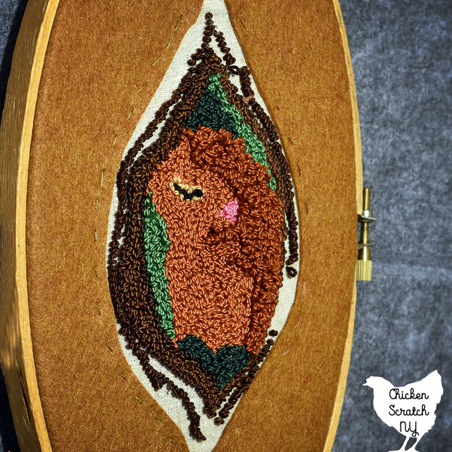 sleeping red squirrel in a tree surrounded by moss, in an oval embroidery hoop with a felt reverse applique frame
